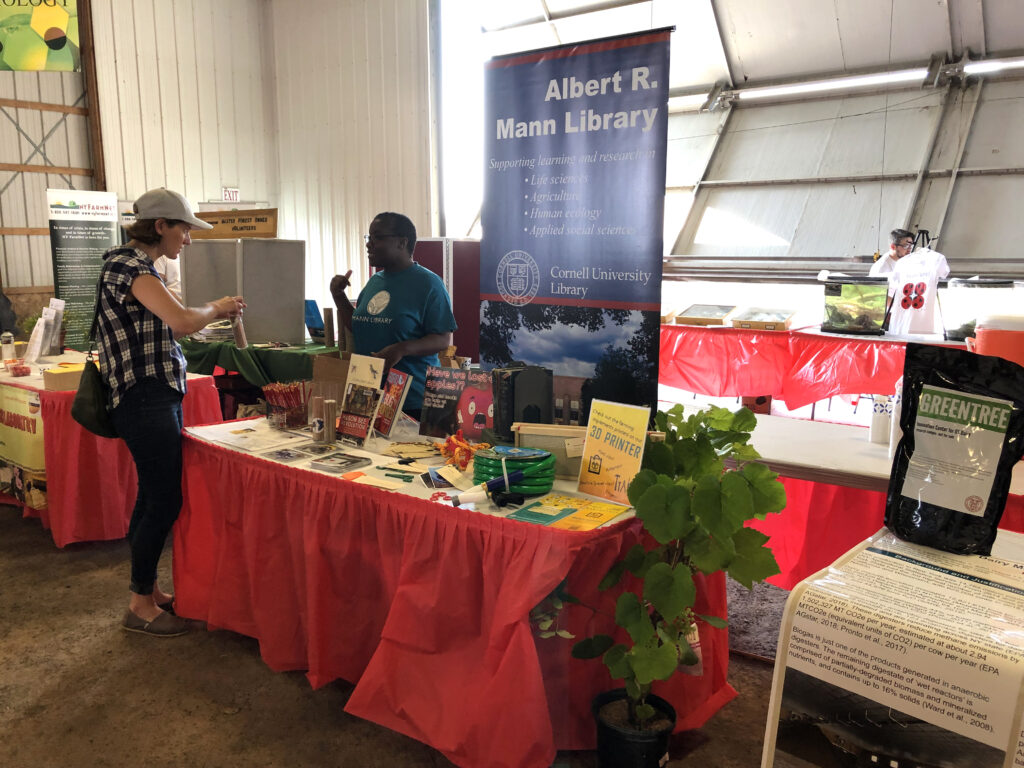 Mann librarian speaking to patron at Empire Farm Days event