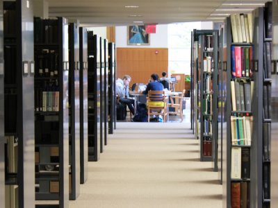 Image of Mann library stacks and students studying